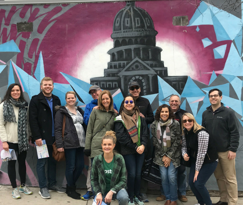 Group posing in front of a Texas State Capital mural