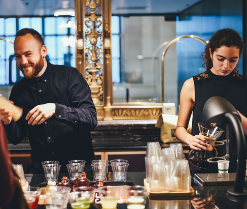 Two bartenders making drinks