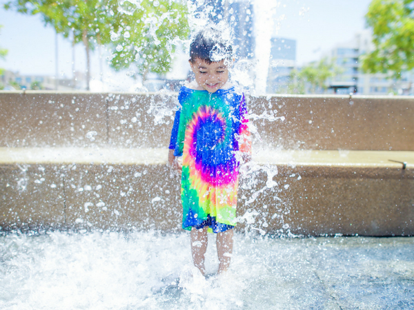 Kid in tie dye shirt playing in water