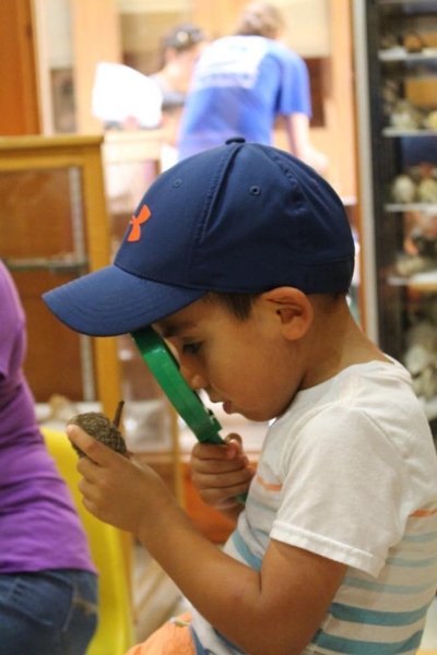 Little boy in blue cap looking through a magnifying glass at an object