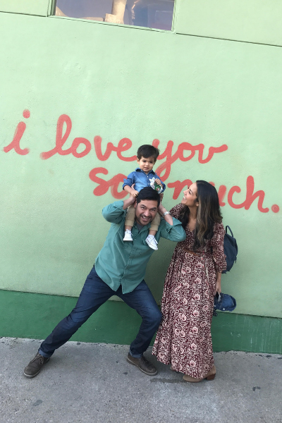 Mom, and dad holding his son on his shoulders in front of the I love you so much mural in Austin Texas