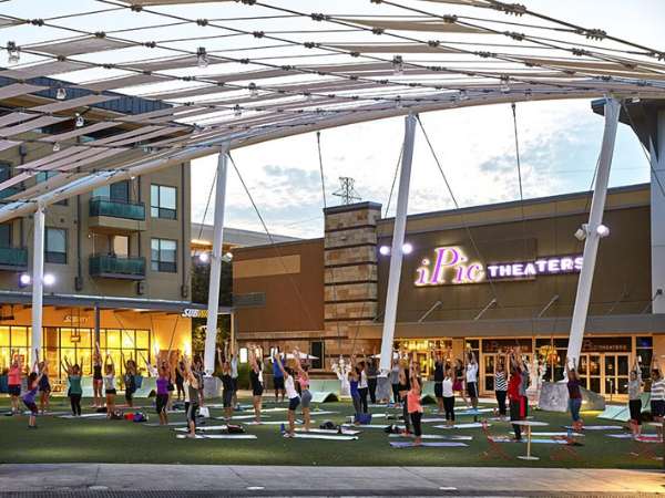 The Domain shopping center with a group of people practicing yoga outside